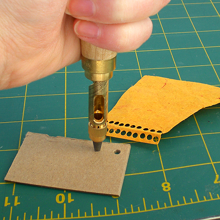this picture gives a good look at the size - relatively small. It probably takes 4 or 5 rotations to make it through board, one to make it through paper and 2 to make it through leather.