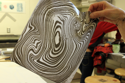 Suminagashi Marbling Class - pulling the paper off of the marbling bath to reveal the print
