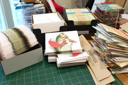 stacks of folded up Merry Fishmas Cards ready for packaging - I hand fold them all too!