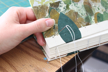 Sewing the cover onto the book with linen thread - The making of a Caterpillar Stitch Book by Ruth Bleakley