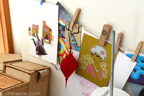 Use a string and clothespins to hang inspirational art in your studio