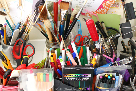 jars used to sort studio items - pens, paintbrushes and markers