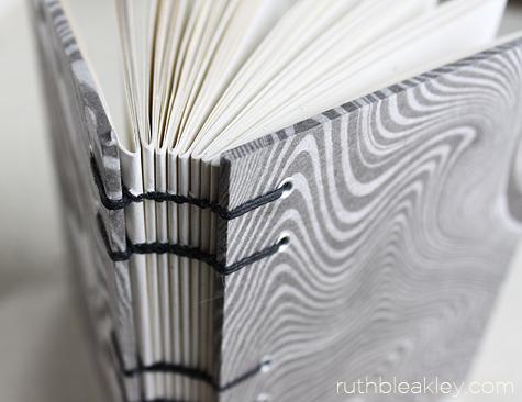 Closeup of stitching on suminagashi journal handmade by Ruth Bleakley