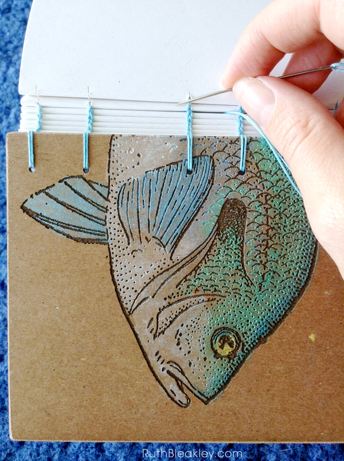 Stitching a journal together - handmade fish book created by Ruth Bleakley